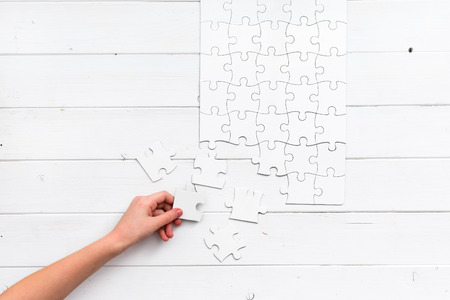 uncompleted: hand holding a piece of white uncompleted puzzle on white wooden background Stock Photo