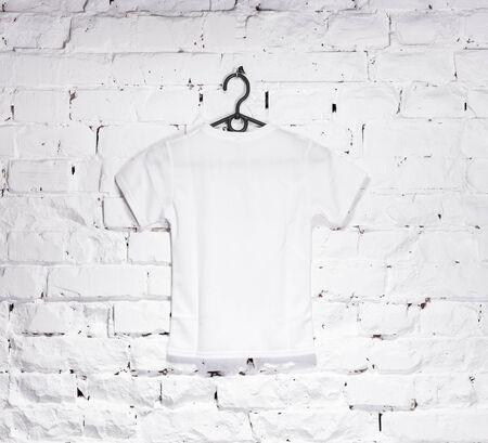 Texture de brique murs blanchis à la chaux avec un t-shirt blanc pour les enfants sur le cintre