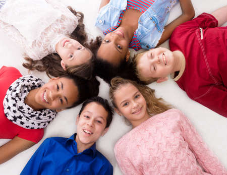 complexion: smiling children with different complexion lying head to head on the floor Stock Photo