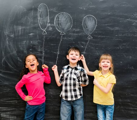 chalky: three joyful laughing children keep imaginary balloons drawn on the chalky blackboard