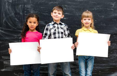 hoja en blanco: tres niños lindos con las hojas de papel en las manos vacías y la pizarra calcárea en el fondo
