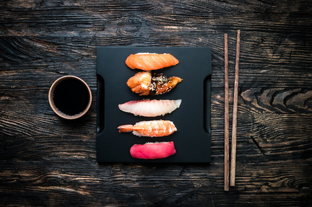 lunch tray: set of sashimi sushi with soy and chopsticks on black wooden background top view Stock Photo