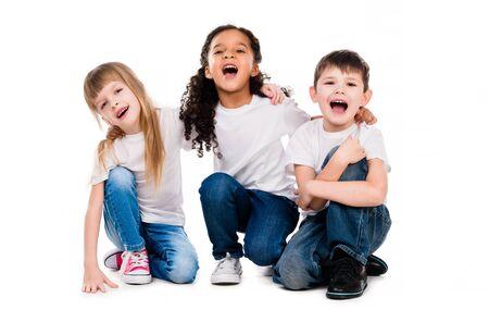 niños sentados: tres hijos de moda divertidas risa sentado en el suelo aislado en el fondo blanco