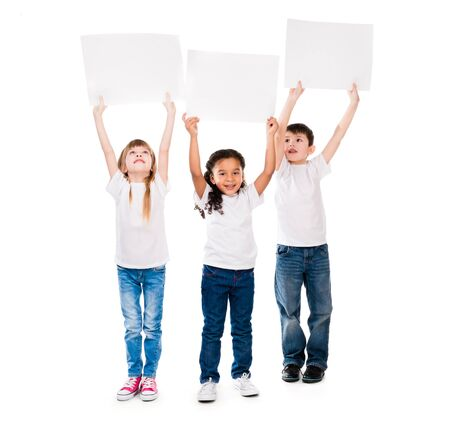 young boys: three cheeerful children holding en empty paper sheet above themselves isolated on white background