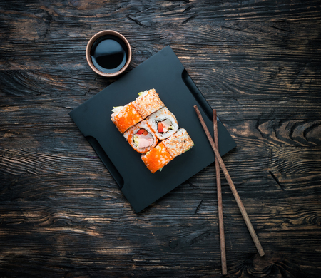 roe: set of sushi rolls with soy and chopsticks on black wooden background top view Stock Photo