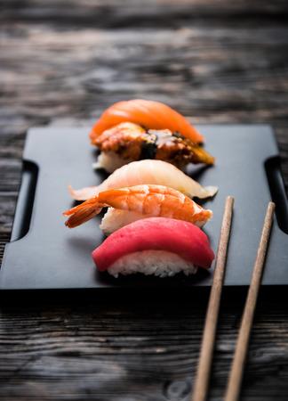 刺身寿司の黒い背景に箸と醤油セット 写真素材
