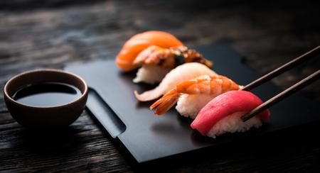 close up of sashimi sushi set with chopsticks and soy on black background Foto de archivo