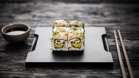 vegetable tray: vegetable sushi rolls on black tray with soy and chopsticks on dark wooden table