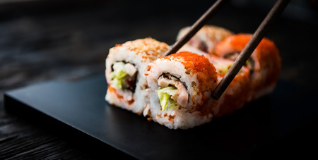 closeup of sushi rolls with chopsticks on dark background