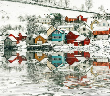 norway: wooden houses on the banks of the Norwegian fjord with reflection in water