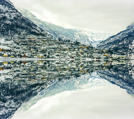 fjords: wooden houses on the banks of the Norwegian fjord with reflection in water