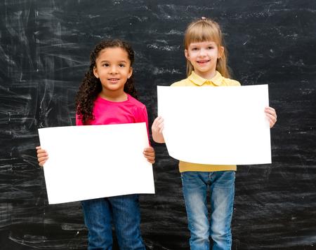 niñas bonitas: dos chicas muy poco con el papel en blanco en las manos y la pizarra calcárea en el fondo