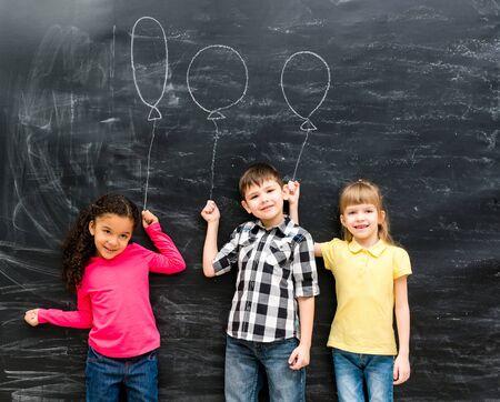 chalky: three joyful laughing children keep imaginary balloons drawn on the chalky blackboard