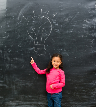 young black girl: smiling little girl pointing at lamp drawn on the blackboard with finger up