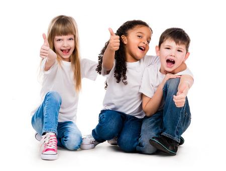 niños sentados: tres hijos divertida que se sienta en el suelo con los pulgares para arriba aislados en el fondo blanco Foto de archivo
