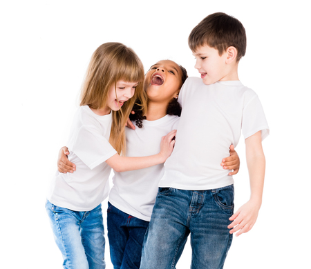 blond girl: three trendy children with different complexion laugh embracing each other isolated on white background