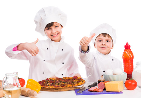 keep out: two smiling little cooks portioning fresh cooked pizza with thumbs up