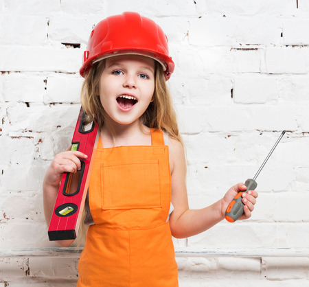 hand tool: pretty girl-worker in helmet with builing level and screwdriver in hands Stock Photo