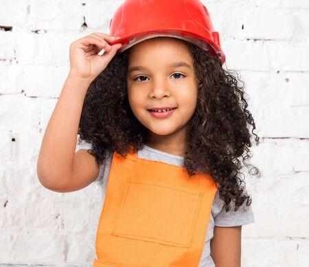 repairmen: cute little girl in orange repairmen uniform and helmet