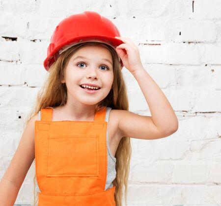 casco rojo: niña sonriente en casco rojo y naranja reparador uniforme