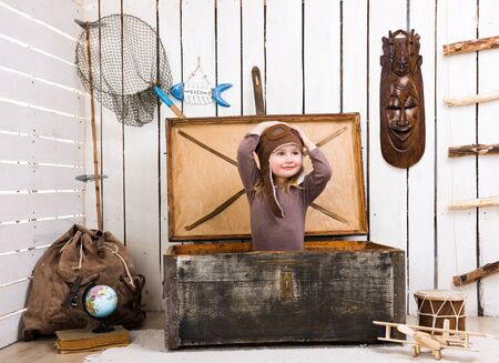 net book: funny little girl-pilot in old wooden chest with hands up