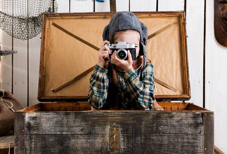 rarity: little girl in pilot hat in wooden chest taking ptoto with rarity camera Stock Photo
