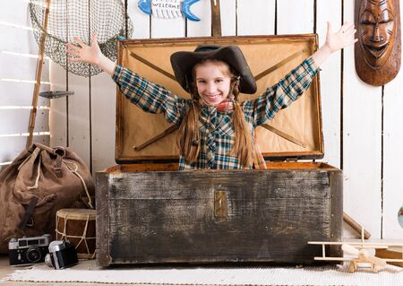 net book: smiling little girl-cowboy with hands up sitting in big old wooden chest Stock Photo