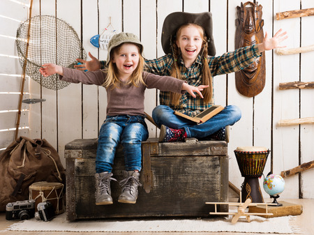 net book: two little girls sitting on big wooden chest with hands up in cowboy hats
