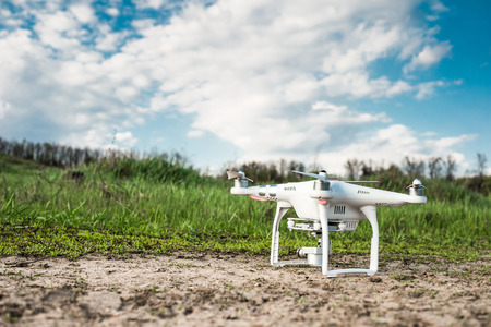 blu sky: white quadrocopter standing on the ground with spring field and blu sky on the background