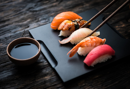 close up of sashimi sushi set with chopsticks and soy on black background Stockfoto
