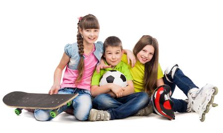 niños sentados: tres niños juguetones lindos que se sientan en el suelo con el material de deporte aisladas en el fondo blanco