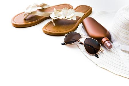 Accessoires de plage. Chaussures d'été et un chapeau avec des lunettes de soleil et de la crème solaire sur fond blanc