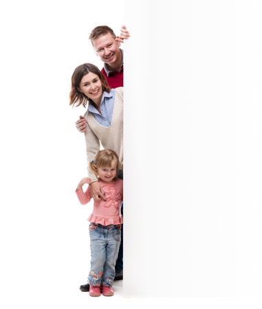 dad and daughter: father, mother and little daughter peek out from behind empty blank isolated on white background