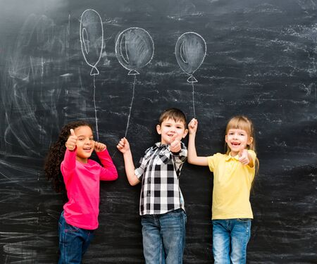 chalky: three smiling children with thumbs up keeping imaginaru drawn balloons on a chalky blackboard