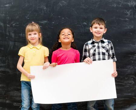 hoja en blanco: tres niños lindos que sostienen una hoja de papel vacía para el anuncio con la pizarra en el fondo calcáreo