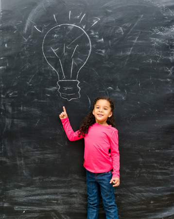 chalky: cute little girl pointing on a drawn lamp on chalky blackboard