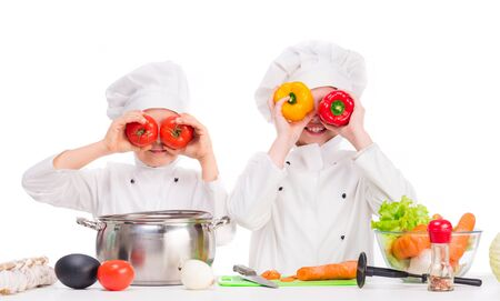 soup bowl: two little cooks in uniform playing vegetables for soup in the kitchen