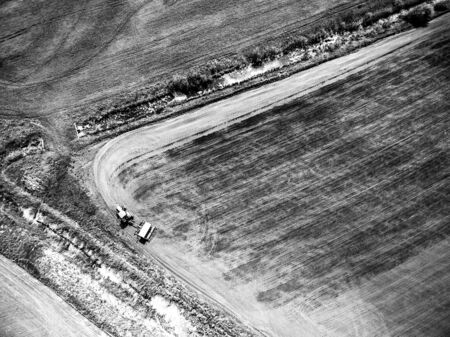 cropland: view from above on harvester plowing field, black and white photo
