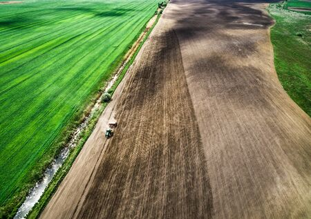 cropland: harvester plowing field in spring, view from height Stock Photo