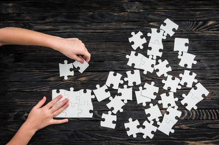 collect: hands starting to collect puzzle pieces on dark wooden table Stock Photo