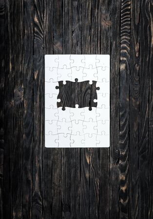 uncompleted: white started puzzle with uncompleted center on dark wooden background