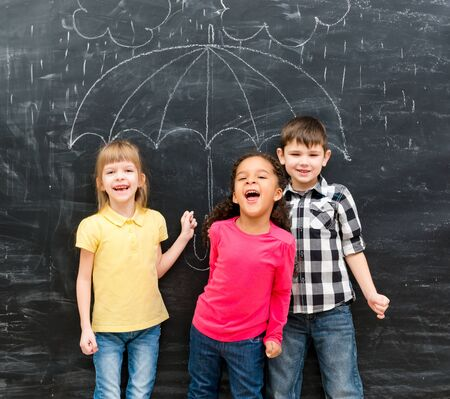 young black girl: three funny laughing children with umbrella drawn on the blackboard on backgorund Stock Photo