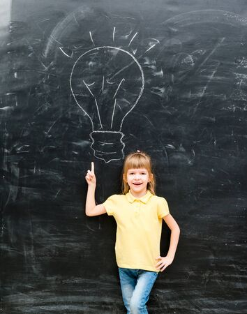 chalky: cute little boy with finger up having an idea with drawn lamp on chalky blackboard