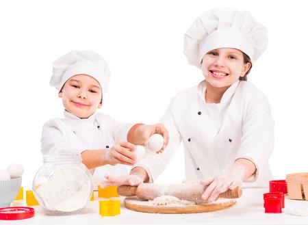 preparing dough: two funny little cooks in white uniform preparing dough in the kitchen
