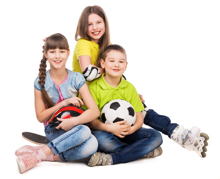 brothers: playful little boy and girls sitting on the floor with ball, skate and rollers isolated on white background Stock Photo