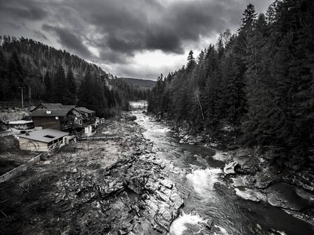 black forest: landscape with mountain river and buildings on bank, aerial black and white photo