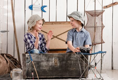 talk big: little boy and girl talk sitting in big old chest