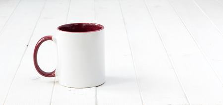 white cup with dark red handle and inside on wooden surface