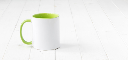 white cup with light green handle and inside on wooden table Stock Photo