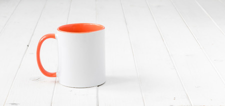 white cup with orange handle and inside on white wooden surface